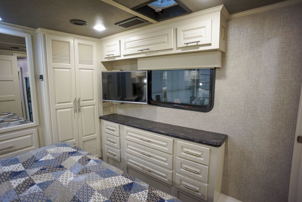 Luxury toy hauler bedroom storage with TV